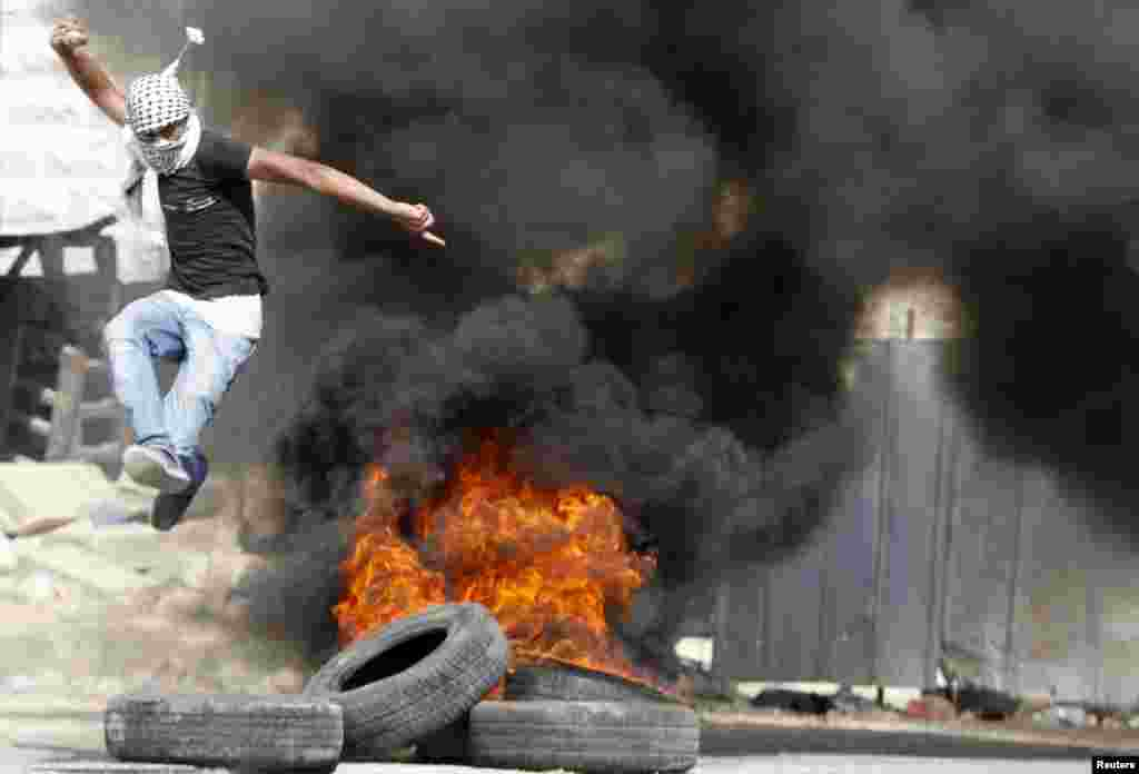 A Palestinian jumps over burning tyres during clashes with Israeli troops in the West Bank city of Hebron on July 31. (Reuters/​Mussa Qawasma)