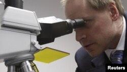 Денсаулық саласы шенеунігі микроскопқа қарап тұр. (Көрнекі сурет)