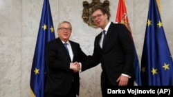 European Commission President Jean-Claude Juncker (left) shakes hands with Serbian President Aleksandar Vucic in Belgrade on February 26.