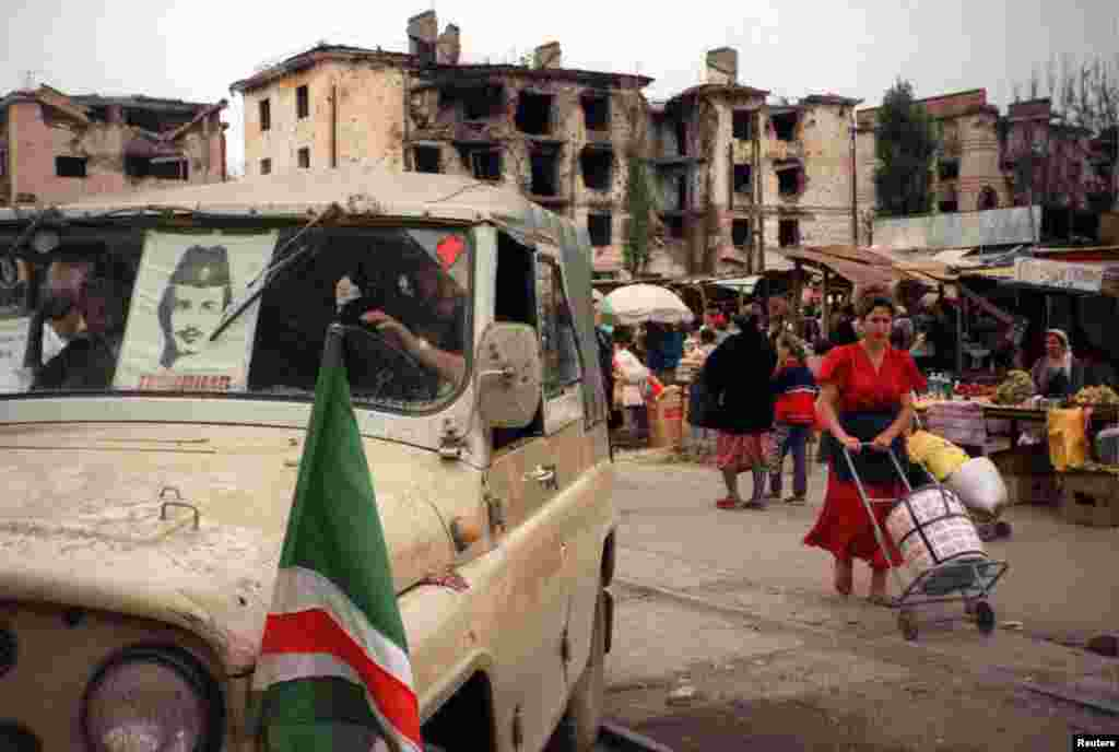 NO - Chechen fighters drive away from the central market place in Grozny - that market place was moved, previously it was located on the end of Mira street