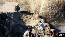 مسلحون من داعش يفحصون حطام طائرة الاردني معاذ الكساسبة
