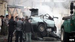 Afghan security officials inspect the site of a bomb blast in Kabul on January 13.