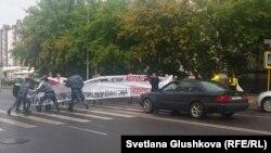 Полицейские разгоняют акцию представителей строительных компаний у акимата города. Астана, 11 августа 2015 года.