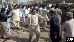 Полиция өкілдері мен тұрғындар жарылыс болған жерде тұр. Сиби, Кветта провинциясы, Пәкістан, 11 қазан 2012 ж.
