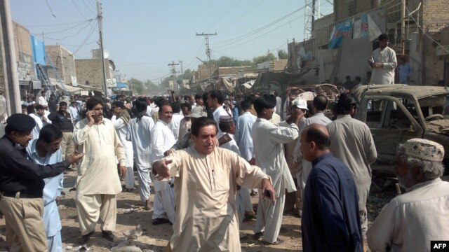 Local Pakistani residents gather at the site of a bomb blast in Sibi, some 180 kilometres southeast of Quetta. At least 10 people died in the explosion.