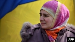 Ukraine - A Crimean Tatar woman stands by a Ukrainian flag as pro-Ukrainian demonstrators march in the streets of Simferopol in support of the Crimean Tatar community, on March 14, 2014