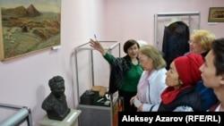 Сотрудница музея рассказывает посетителям выставки о демонстрируемых экспонатах. Алматы. 22 апреля 2019 года.