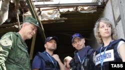 Members of the OSCE Special Monitoring Mission (SMM) to Ukraine in a grain depot destroyed in a shelling attack in Dokuchaievsk, Ukraine, in 2016.