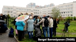 Journalistst gather outside a school where a teenager fired shots and tossed smoke grenades, in Ivanteyevka, a town in the northeastern suburbs of Moscow, on September 5.