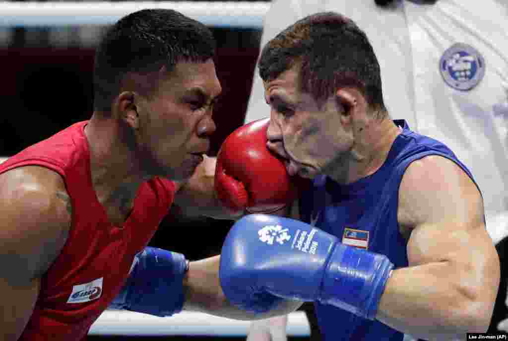 The Phillippines' Eumir Felix Marcial (left) and Uzbekistan's Israil Madrimov fight in their men's middleweight boxing semifinal at the 18th Asian Games in Jakarta, Indonesia. Marcial lost in a split decision. (AP/Lee Jin-man)