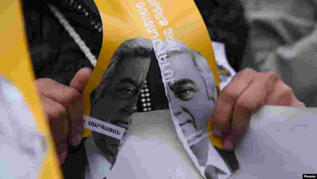 Протестующий рвет плакат с изображением Сержа Саргсяна и данным им в 2014 году обещанием больше не занимать руководящую должность.
