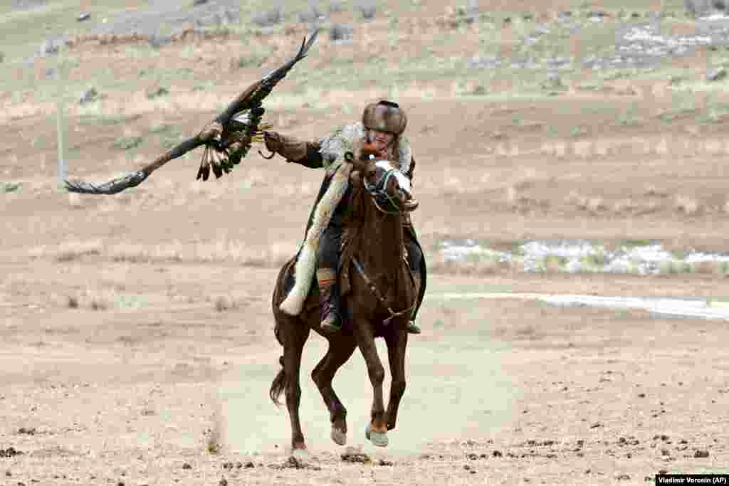 A Kyrgyz man rides a horse holding a golden eagle during a hunting festival in a small mountain village about 250 kilometers southeast of Bishkek. (AP/Vladimir Voronin)