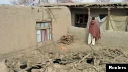 An Afghan man stands on the roof of a house damaged in an air strike in Nangarhar Province on February 21.