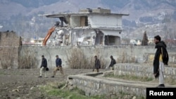 Policemen walk past as demolition work continues on February 26 on the building where Al-Qaeda leader Osama bin Laden was killed by U.S. special forces in May 2011.