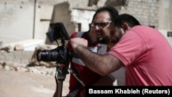 Syrian director Humam Husari (right) films a scene in a rebel-held district in the Damascus suburbs in September 2016.