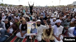 A man holds a picture of Mumtaz Qadri as he chants slogans with others during a sit in protest against Qadri's execution in front of the Parliament building in Islamabad, Pakistan, on March 29.