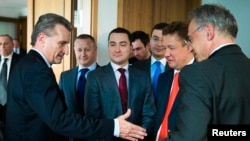 European Energy Commissioner Guenther Oettinger (left) reaches out to shake hands with Gazprom Chief Executive Aleksei Miller (second from right) as Gazprom representative Sergey Kupriyanov (center) looks on after EU-Ukraine-Russia energy negotiations at the EU commission representation in Berlin on May 30.