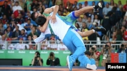 Wrestler Ikhtiyor Navruzov of Uzbekistan celebrates with his coach after winning a bronze medal.
