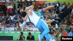 Wrestler Ikhtiyor Navruzov of Uzbekistan celebrates with his coach after winning a bronze medal.