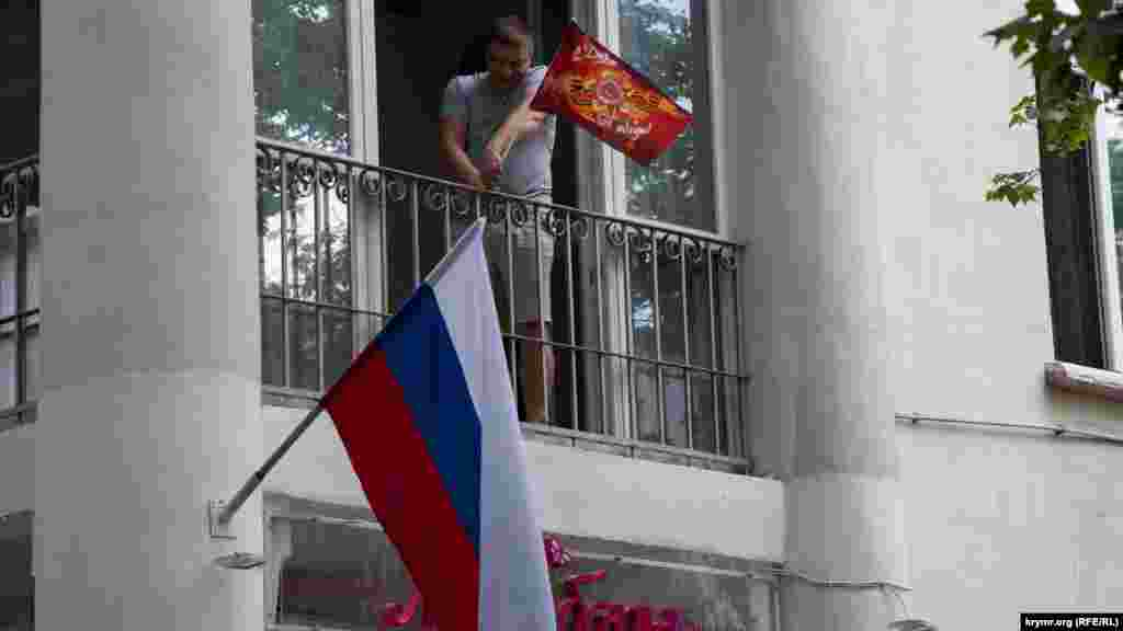 Yerli sakinler ve ofislerniñ hadimleri Rusiye bayraqları yanında sovet simvolikası ile ufaq bayraqlarnı asalar
