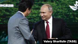 Російський президент Володимир Путін запропонував прем'єр-міністру Японії Сіндзо Абе (л) укласти мирну угоду