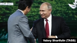 Japanese Prime Minister Shinzo Abe (left) shakes hands with Russian President Vladimir Putin during a session of the Eastern Economic Forum in Vladivostok on September 12.