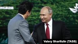 Shinzo Abe (solda) və Vladimir Putin