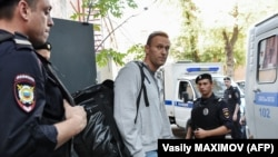 Russian opposition leader Aleksei Navalny is escorted by police after his trial at a Moscow courthouse on August 27.
