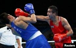 Данияр Елеусинов (слева) уходит от удара соперника из Узбекистана Шахрама Гиясова. Рио-де-Жанейро, 17 августа 2016 года.