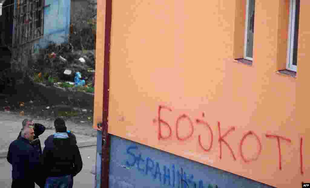 A group of ethnic Serbs stand near graffiti in Mitrovica calling for an election boycott.