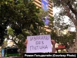 """Участник акции протеста в Тель-Авиве на фоне """"Дома Жаботинского"""" и баннера с Нетаньяху и Путиным"""