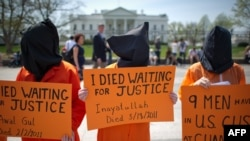 U.S. -- Black hooded human rights activists hold banners demanding the closing of Guantanamo during a protest, part of the Nationwide for Guantanamo Day of Action, outside the White House in Washington DC on 11Apr2013