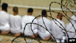 A group of detainees kneels during early morning Islamic prayer at the Guantanamo camp