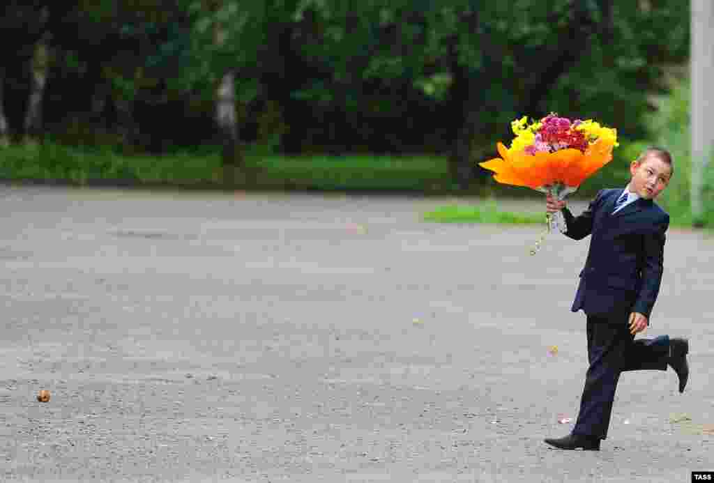A Russian boy walks with a bouquet of flowers for his teacher on the first day of school in Ivanovo. (ITAR-TASS/Vladimir Smirnov)
