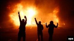 Демонстранттар өрттөлгөн дүкөндүн жанында. Фергюсон, 24-ноябрь, 2014-жыл.
