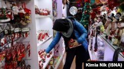 An Iranian woman shopping Christmas items in a store in central Tehran, on Wednesday, December 26, 2018.