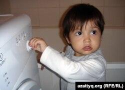 """""""Ақ бесік"""" қоғамдық қорының негізінде құрылған шағын орталыққа келуші балалардың бірі Дания кір жуатын машинаны қызықтап тұр. Ақтөбе, 27 тамыз 2012 жыл."""