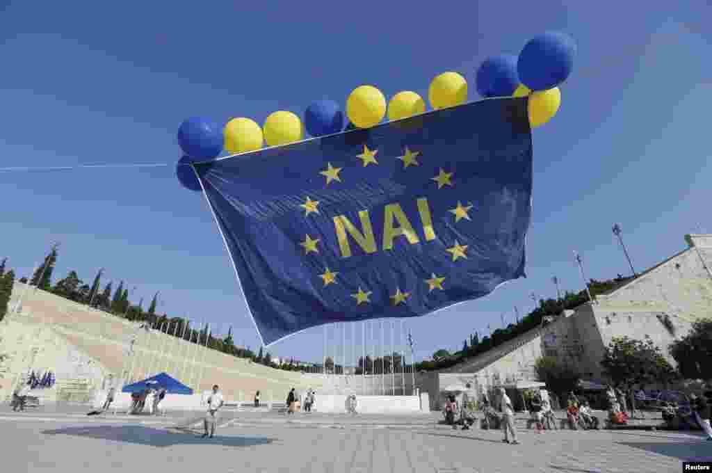 """Флаг ЕС с надписью """"ДА"""" запустили в воздух участники митинга сторонников сотрудничества с кредиторами на митинге в Афинах 3 июля."""