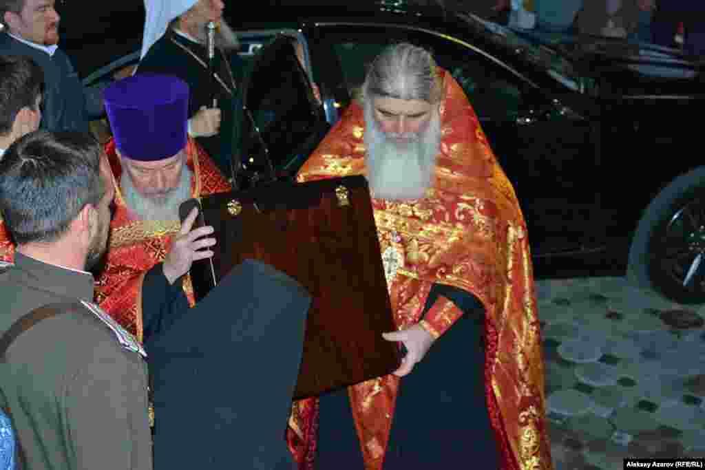 Икону в футляре из машины несут в сестринский корпус монастыря. Отсюда должен начаться крестный ход с иконой к собору.