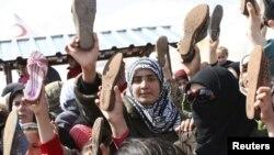 Türkiyədə məskunlaşan suriyalı qaçqınlar ayaqqabılarını çıxarıb Bashar Assad rejiminə etirazlarını bildirirlər. 15 mart 2012