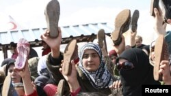 Refugjatët sirianë protestojnë me këpucë në dorë kundër presidentit Bashar al-Asad në kampin e refugjatëve Hataj në Turqi