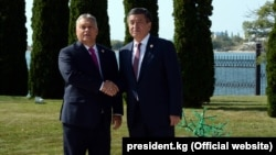 Hungarian Prime Minister Viktor Orban (left) and Kyrgyz President Sooronbai Jeenbekov shake hands on September 3.