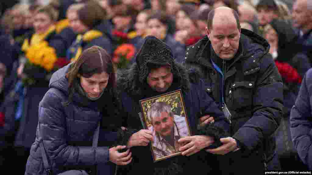Relatives hold a picture of Flight PS572 pilot Volodymyr Haponenko. He is survived by his wife and two daughters.