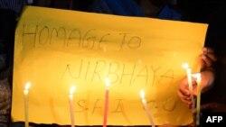 Индийские студенты держат плакаты и свечи в память о жертве группового изнасилования после вынесения приговора четырем обвиняемым.