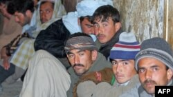 Detained Afghan immigrants sit in a Pakistani security cell in Quetta, just some of the thousands who flee the country every year.