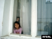Children of Kazakh asylum seekers peek out of their dormitory in Brno, Czech Republic
