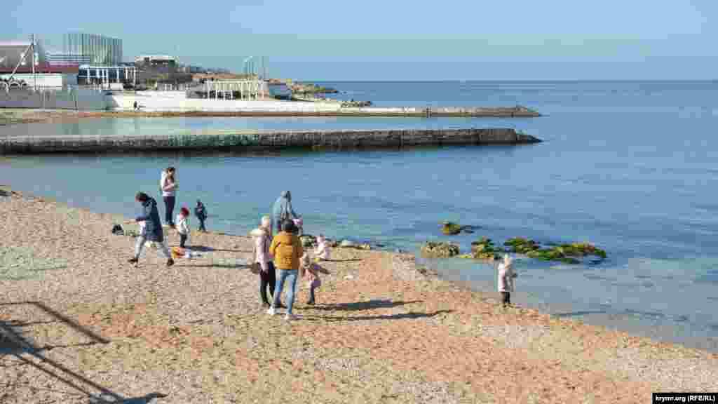 На пляже и взрослые, и дети заняты своими делами