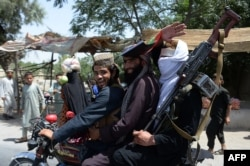 Taliban militants ride on a motorbike as they took to the streets to celebrate a cease-fire on the second day of Eid on the outskirts of Jalalabad on June 16.