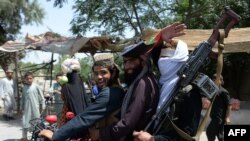 Taliban militants ride a motorbike as they took to the street to celebrate ceasefire in Jalalabad on June 16.