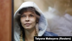 Anastasia Vashukevich, also known as Nastya Rybka, sits inside a defendants' cage before a court hearing in Moscow on January 19.